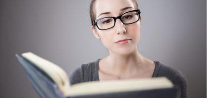 pani czyta książkę, słownik